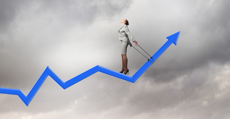 roped: Young businesswoman with ropes on hands standing on graph