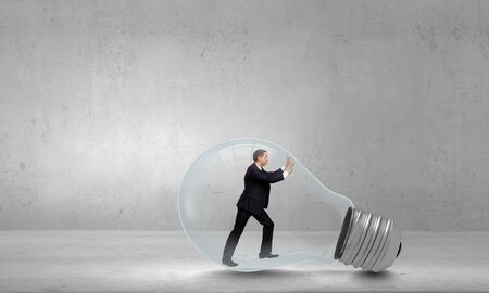get out: Businessman inside light bulb trying to get out