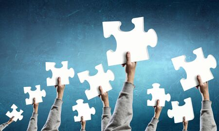 teamworking: Human hands holding colorful jigsaw puzzle elements Stock Photo