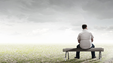man looking at sky: Fat man sitting on bench with his back and looking away