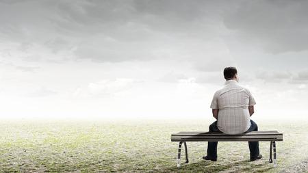 Hombre gordo sentado en el banco con la espalda y mirando de lejos Foto de archivo - 45437697