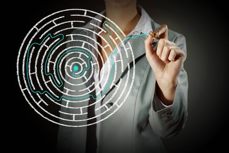 difficult to find: Close up of businessman drawing way out of labyrinth Stock Photo