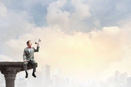 megafono: Hombre de negocios sentado en la parte superior y gritando en el megáfono