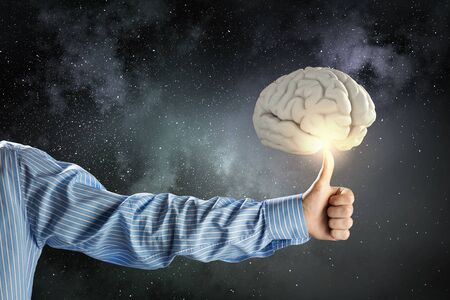 strengthen hand: Close up of businessman hand showing thumb up to brain