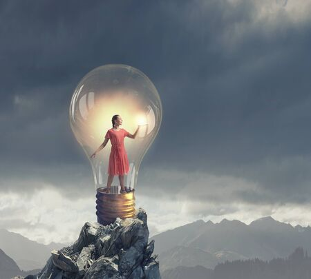 broaden: Young woman in red dress with book in hand inside light bulb Stock Photo