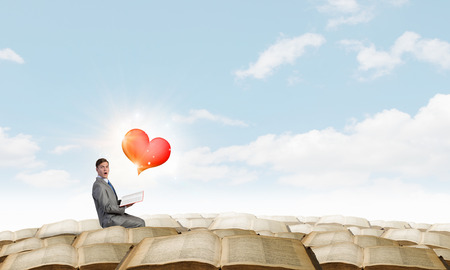 emotional love: Young emotional businessman with opened book in hand