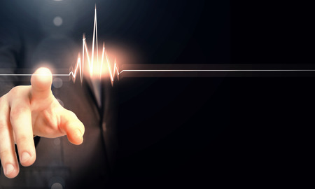 beats: Male hand touch heart pulse on futuristic interface Stock Photo