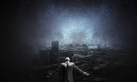 dark city: Businessman with hands spread apart on city landscape background