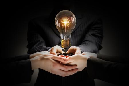 tormenta de ideas: Lluvia de ideas y trabajo en equipo concepto con hombres de negocios diversos que sostiene la bombilla en manos
