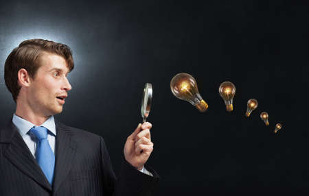 botanist: Young businessman looking in magnifying glass at glass light bulb