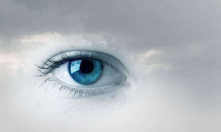 closeup: Female blue eye on cloudy sky background