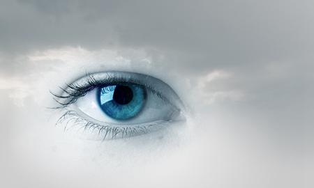 Female blue eye on cloudy sky background