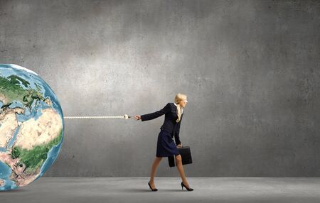 business globe: Young businesswoman with suitcase pulling Earth planet with lead.