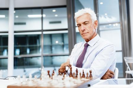 jugando ajedrez: Hombre de negocios en la oficina de juego de ajedrez