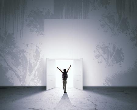 abrir puerta: Vista trasera de la mujer con las manos en alto entrando puerta abierta Foto de archivo