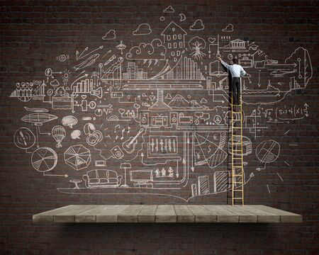 business ideas: Back view of businessman standing on ladder and drawing sketch on wall