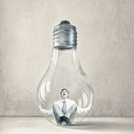 Screaming businessman trapped inside of light bulb Stock Photo
