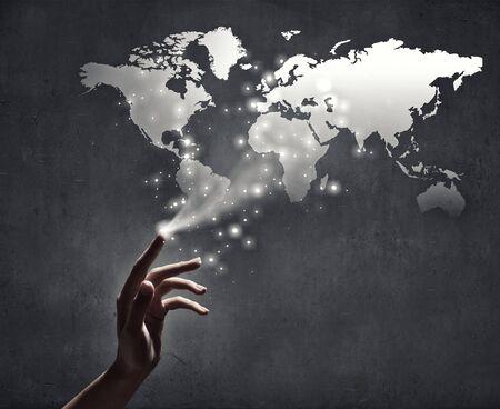 schöpfung: Nahaufnahme der menschlichen Hand berühren mit dem Finger Weltkarte Lizenzfreie Bilder