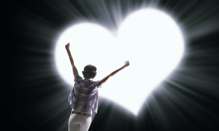 true: Rear view of woman with hands up in light of love
