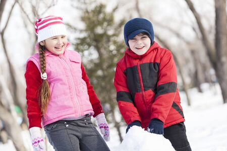 cheerful teen girl: Cute boy and girl building snowman in winter park Stock Photo