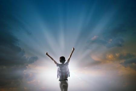 mujer alegre: Volver la vista de mujer alegre con las manos en alto mirando la salida del sol Foto de archivo