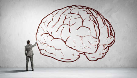 broaden: Back view of businessman drawing human brain on wall Stock Photo