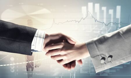 technology agreement: Close up of business handshake on digital background