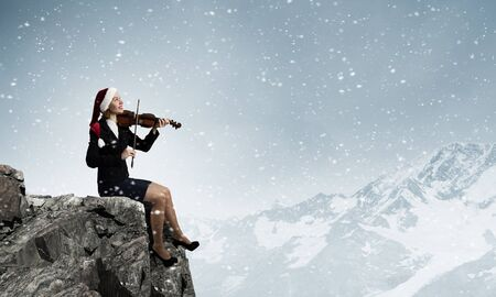 express positivity: Woman in formal suit and Santa hat playing violin