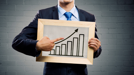 black board: Unrecognizable businessman holding chalkboard with growth arrow concept