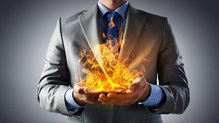 llamas de fuego: Hombre de negocios la celebración de las llamas del fuego jóvenes en las palmas