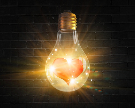 electric bulb: Glowing light bulb and red heart inside of it Stock Photo