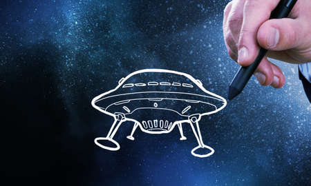 ufology: Person hand drawing UFO ship on space background Stock Photo