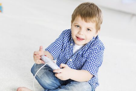 baby boys: Boy sitting on floor and palying with joystick