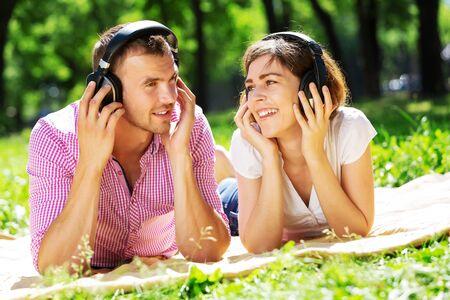 escuchando musica: Amar a dos jóvenes en la música parque escucha verano Foto de archivo