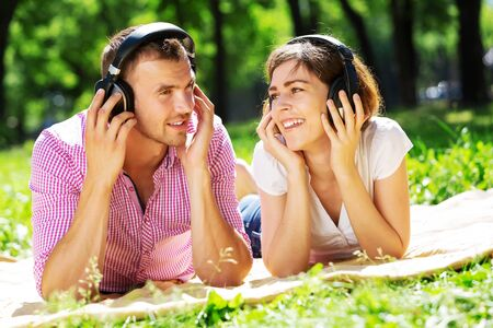 listening music: Loving young couple in summer park listening music