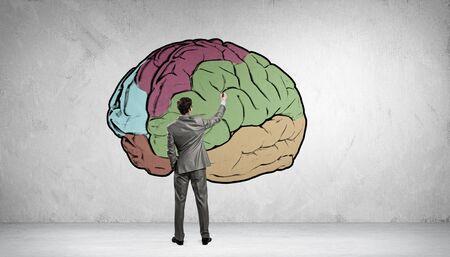 cerebro: Vista posterior del empresario dibujo cerebro humano en la pared