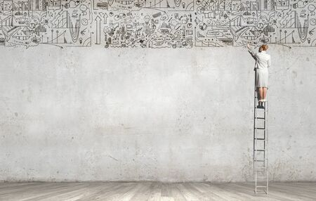 business ideas: Rear view of woman standing on ladder and drawing science sketch on wall