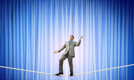 juggling: Young businessman balancing on rope and juggling with balls