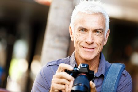 Senior man with camera in city Stock Photo