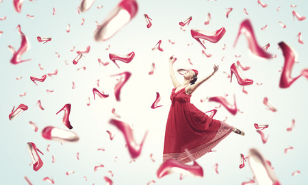 red shoes: Young cheerful woman in dress and many falling shoes