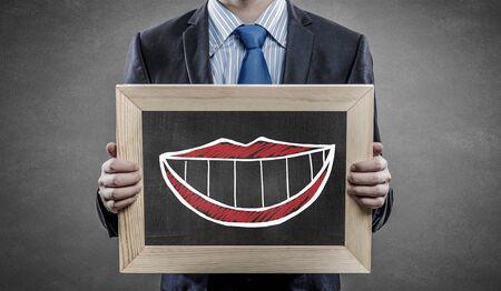 smilie: Unrecognizable businessman holding chalkboard with drawn smilie