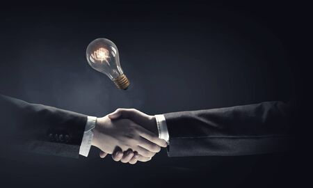 stretta mano: I partner commerciali stretta di mano e lampadina incandescente Archivio Fotografico