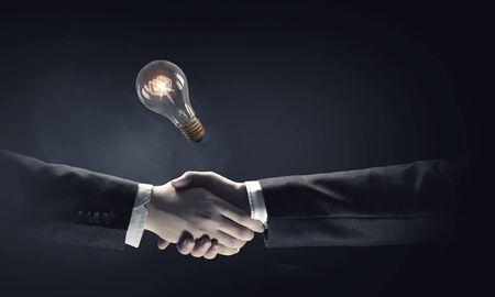 apreton de manos: Los socios comerciales del apretón de manos y la bombilla de luz incandescente