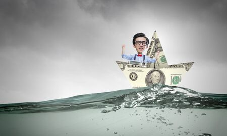 risky job: Businessman escapes from crisis on paper boat made of dollar banknote