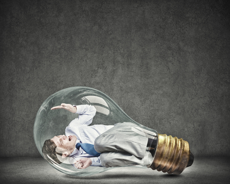panicked: Screaming businessman trapped inside of light bulb Stock Photo
