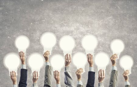 management team: Many human hands holding light bulb signs