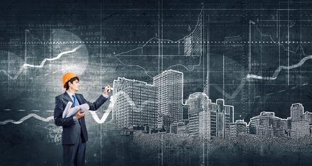 Junger Mann Ingenieur im Sturzhelmzeichnung Bauvorhaben Standard-Bild
