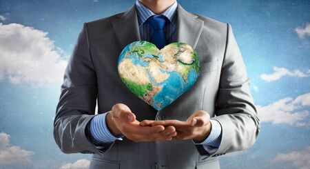 Businessman hands holding Earth planet. Elements of this image are furnished by NASA