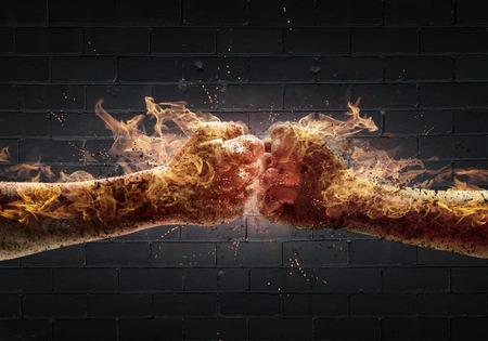 enojo: Cerca de dos puños en el fuego golpeando entre sí