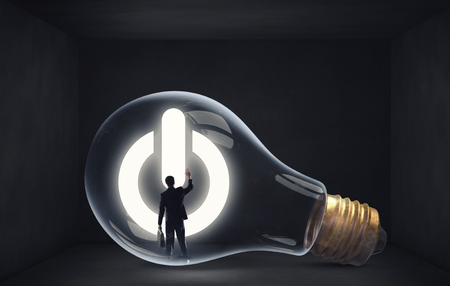 concept and ideas: Man holding luminous idea inside light bulb